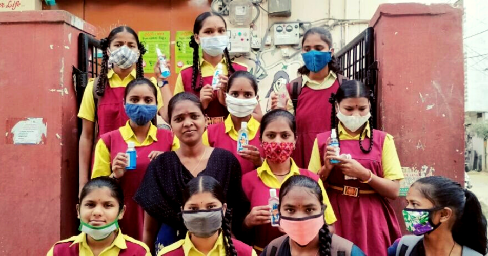A group of Indian schoolgirls in masks, some holding up hand sanitiser